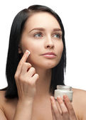 Woman applying moisturizing cream — Stock Photo