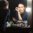 Постер, плакат: Woman applying makeup
