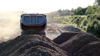 A dump truck dumps a pile of soil in mountains of soil — Stockvideo
