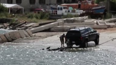 Speed boat docking at shore where a black family truck is waiting for the boat — Vídeo de stock