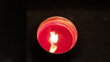 A red melting candle light inside a round glass — Vidéo