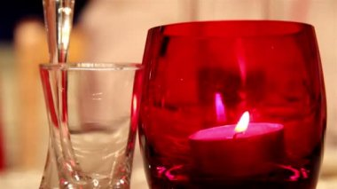 A candlelight inside a red glass and a small glass — Vídeo Stock