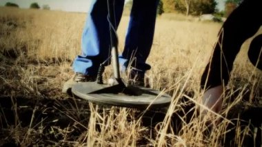 Holding the metal detector grass cutter — Stock Video