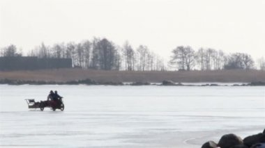 A motorcycle motorbike mobile car is so fast pulling a sled on snow — Stock Video