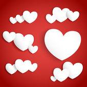 Coeurs de papier blanc sur fond rouge — Vecteur