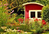 An idyllic garden place with a red house — Stock Photo