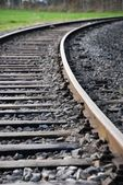 Single railway track which turns — Stock Photo