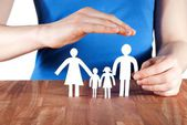Hand protecting a family — Stock Photo