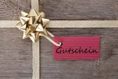 Golden bow with red tag with Gutschein — Stock Photo