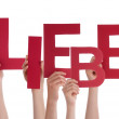 Stock Photo: Persons Holding Liebe