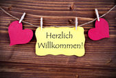 Yellow Label with Herzlich Willkommen — Stock Photo