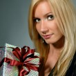 Beautiful blond holding gift box. — Stock Photo