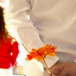 Man hiding flower to surprise his girlfriend — Stock Photo