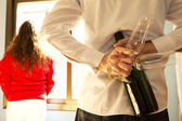 Man hiding champagne glasses and champage to surprise his woman — Stock Photo