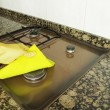 Womcleaning burner in kitchen with yellow cloth — Stock Photo #21775575