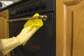 Female arms only cleaning the outside of an oven — Stock Photo