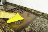 Woman cleaning burner in the kitchen with yellow cloth — Stock Photo
