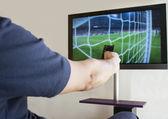 Hand holding TV remote control — Stockfoto
