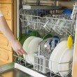 Young womin Kitchen doing Housework with dishwasher — Stok Fotoğraf #22224591