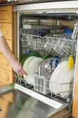 Young woman in the Kitchen doing Housework with the dishwasher — Stock Photo