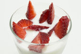 Glass of yogurt with strawberries isolated on white in close up — ストック写真