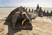 Sand dragon cast by children on the beach — Stock Photo