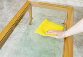 Cleaning a glass table with yellow cloth — Stockfoto