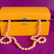 Stock Photo: Pearl necklace in old box orange