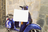 Motorcykel parkerad vid en stenad vägg — Stockfoto