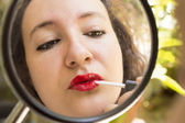 Woman applying lipstick in the mirror of a motorcycl — Stock Photo