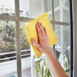 Woman cleaning a window with yellow cloth — Stock Photo #25097167