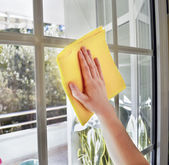 женщина, очистка окно, с желтым ткань — Стоковое фото
