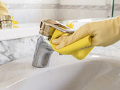 Cleanig tap with yellow gloves — Stock Photo