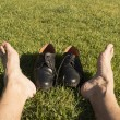 Feet relaxing in the grass with his shoes — Stock Photo