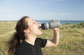 Casual woman drinking after training — Stock Photo