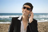 Latin lover calling by phone on the beach — Stock Photo
