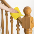 Cleaning wooden railing with yellow cloth — Stock Photo