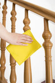 Cleaning wooden railing with yellow cloth vertical — Stock Photo