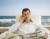Man commenting economy news on the beach — Stock Photo