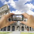 Tourist holds up camera mobile at coliseum in Rome — Stock Photo