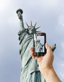 Tourist holds up camera phone at statue of liberty — Stock Photo