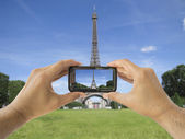 Tourist holds up camera phone at eiffel tower — Stock Photo