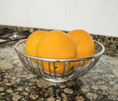 Three oranges in a container — Stock Photo