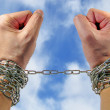 Hands with chains on sky backgroun — Stock Photo #28267019