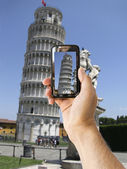 Tourist holds up camera phone at Leaning Tower of Pisa — Stock Photo