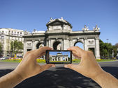 Tourist holds up camera phone at Puerta de Alcala in Madrid — Stock Photo