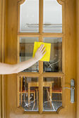 Cleaning a wood and glass door — Stock Photo