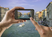 Tourist holds up camera phone at the grand canal — Stock Photo