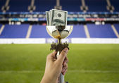More dollars more titles with the background of a stadium — Stock Photo