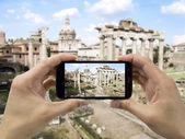 Tourist holds up camera mobile at forum in Rome — Stock fotografie